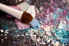 Eyeshadow make-up powder and brush, shallow dof. A still-life of colourful eyeshadow powder and make-up brush stock images