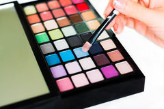 Eyeshadow palette closeup with a woman hand Royalty Free Stock Photos