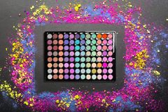 Eyeshadow palette with colorful eyeshadows crumbled on black background. Flat lay. Top view stock photography
