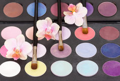 Eyeshadow palette cosmetic brushes for makeup and orchid flowers. Royalty Free Stock Images
