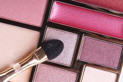 Eyeshadow in pink tones and lip gloss and applicator close-up. Macro Royalty Free Stock Photo