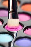 Eyeshadow set with makeup brush picking up color. A close-up image of a eye-shadow kit, with a professional makeup brush picking up some pink colour Royalty Free Stock Photo