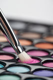 Eyeshadow set with makeup brush picking up color. A close-up image of a eye-shadow kit, with a professional makeup brush picking up some pink colour Royalty Free Stock Photography