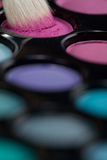 Eyeshadow set with makeup brush picking up color. A close-up image of a eye-shadow set, with a professional makeup brush picking up some pink colour Stock Photo