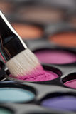 Eyeshadow set with makeup brush picking up color. A close-up image of a eye-shadow set, with a professional makeup brush picking up some pink colour Stock Image