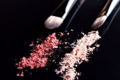 Eyeshadow and two brushes on black background. Set of cosmetics. On dark stock image