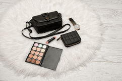 Eyeshadow, wallet, lipstick, watch and black handbag on a white fur. Fashion concept Royalty Free Stock Photos