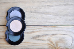 Eyeshadows in black boxes and brush on wood table Stock Photo