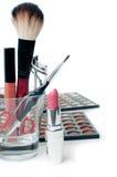 Eyeshadows, lipstick, eyelash curlers and  make-up brushes Stock Photography