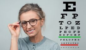 Eyesight check. Woman in glasses on the background of eye test chart. Optician. Eyesight check. Woman in glasses on the background of eye test chart, eye care Royalty Free Stock Photography