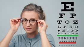 Eyesight check. Woman in glasses on the background of eye test chart. Optician. Eyesight check. Woman in glasses on the background of eye test chart, eye care Royalty Free Stock Images