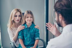 Eyesight and healthcare concept. Rear view of male optician talk. Ing to patients in his ophthalmology office , blond cute women and her small pretty daughter stock images
