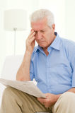 Eyesight problems. Senior man having trouble with eyesight while reading a newspaper at home Royalty Free Stock Photos