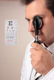 Eyesight vision assessment. An eye doctor using an opthalmoscope device during an eyesight examination Royalty Free Stock Photos