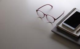 Eyeware und der Smartphone über dem weißen Tabellenraum Lizenzfreie Stockfotos