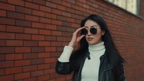 Ασιατικοί περίπατοι γυναικών κατά μήκος της πόλης σε eyewear φιλμ μικρού μήκους