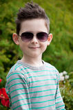 Eyewear concept. Stylish baby boy with dark hair in trendy sungl. Asses and in a striped polo-neck, the  standing, in the park with green grass. Hipster style Stock Photography
