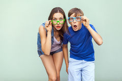 Eyewear concept. WOW faces. Young sister and brother with freckles on their faces, wearing trendy glasses, posing over light green. Background together. Looking stock photos