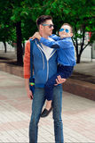 Eyewear concept. Young stylish father with the young cheerful  s. On. They are walking city street. Hipster style. Sunny weather. Outdoor shot Stock Photos
