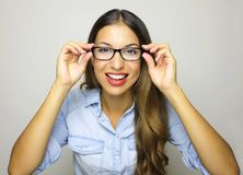 Eyewear glasses woman portrait. Smiling woman wearing glasses and holding frame. Beautiful young mixed race female model on gray stock images