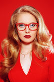 Eyewear style. Beautiful young woman with magnificent blonde hair wearing red dress and elegant red glasses. Beauty, fashion. Optics, eyewear. Red background Stock Photography