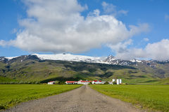 Eyjafjallajokull volcano in Iceland against blue summer sky. With clouds. Farm Thorvaldseyri and path visible stock images