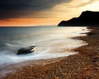 Eype Beach Sunset. The Sun setting behind the picturesque cliffs of Eype beach in Dorset. A long exposure has resulted in soft movement in the waves as they stock photo