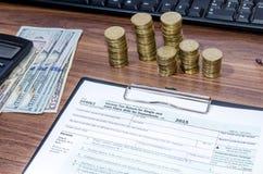 1040EZ inkomstenbelastingsvorm met geld, pen Stock Foto's