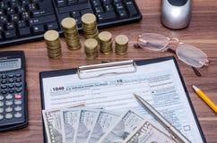 1040EZ inkomstenbelastingsvorm met geld, pen Stock Foto