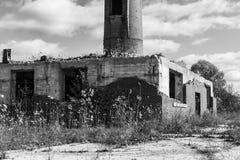 Fábrica abandonada con la chimenea del ladrillo y los remanente de la central eléctrica I Imagenes de archivo