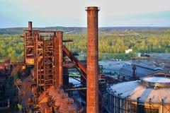 Fábrica abandonada de las industrias siderúrgicas - chimenea oxidada iluminada por el sol por el sol