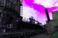 Fábrica abandonada que emite niebla con humo de la producción de la radiación al cielo púrpura venenoso brillante, el concepto de fotos de archivo libres de regalías
