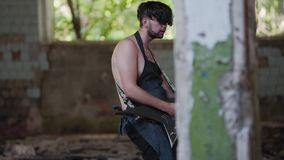Fábrica abandonada quebrada El guitarrista hace una parte en el territorio del edificio abandonado quebrado almacen de metraje de vídeo
