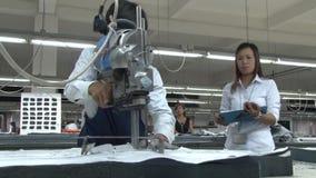 Fábrica asiática da indústria de vestuário: Cortes do trabalhador com o supervisor próximo vídeos de arquivo