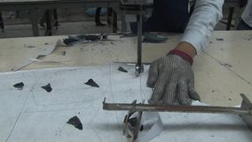 Fábrica asiática da indústria de vestuário: Luva metálica do CU quando o trabalhador cortar a tela vídeos de arquivo
