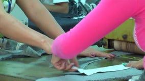 Fábrica asiática da indústria de vestuário: Material da alimentação de mãos do CU no rolo filme
