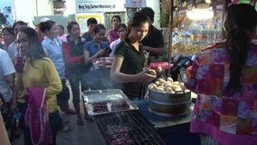 Fábrica asiática da indústria de vestuário: Os trabalhadores de vestuário do MS no fim do dia compram o alimento vídeos de arquivo