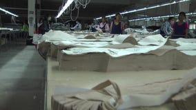 Fábrica asiática da indústria de vestuário: Rusga da câmera ao longo das partes cortadas da tela vídeos de arquivo