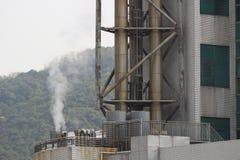 fábrica con las pilas de humo en HK Foto de archivo