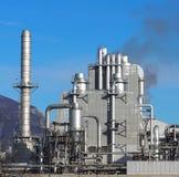 Fábrica con una chimenea larga del metal y muchos tubos alrededor de un edificio industrial fotos de archivo