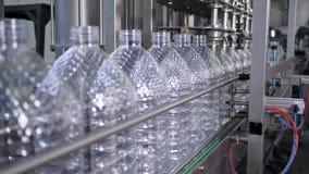 Fábrica da água, água de mola pura de engarrafamento em garrafas plásticas na planta filme