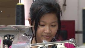 Fábrica da roupa de matéria têxtil: Trabalhador de vestuário fêmea na máquina de costura video estoque