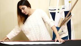 Fábrica de costura Una mujer trabaja para una compañía de la adaptación La costurera revela el paño para el modelo metrajes