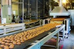 Fábrica de la confitería Cadena de producción de las galletas de la hornada Foco selectivo imagenes de archivo