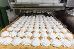 Fábrica de la confitería, producción de la industria alimentaria Bandeja con la melcocha o céfiro hecho por equipmen automatizado foto de archivo libre de regalías