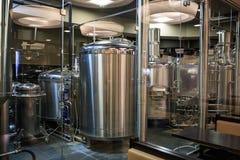 Fábrica de la fabricación de la cervecería Cubas o los tanques del acero inoxidable con los tubos, pequeño equipo de la elaboraci fotografía de archivo