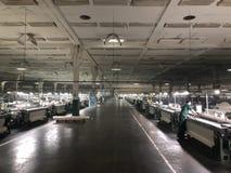 Fábrica de la materia textil desde adentro con muchas máquinas para hacer punto foto de archivo