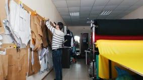 Fábrica de la ropa Un hombre que toma plantillas de la pared metrajes