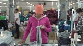 Fábrica do vestuário de matéria têxtil: As preparações eretas do trabalhador de vestuário terminaram o vestuário filme