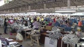Fábrica do vestuário de matéria têxtil: Bandeja larga do tiro através do assoalho e da posse da fábrica do vestuário filme